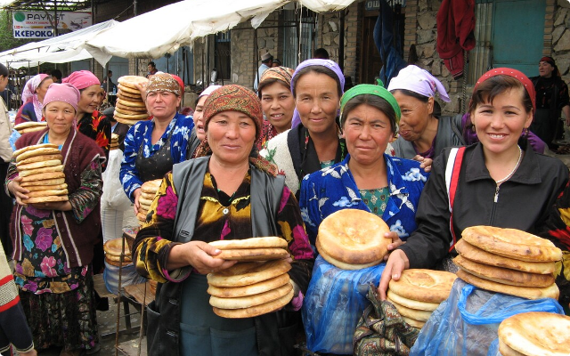 Uzbek women buying bread at a market.