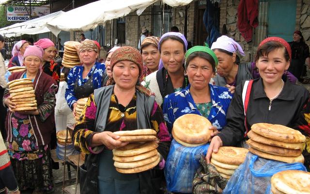 Uzbek women buying bread at a market.